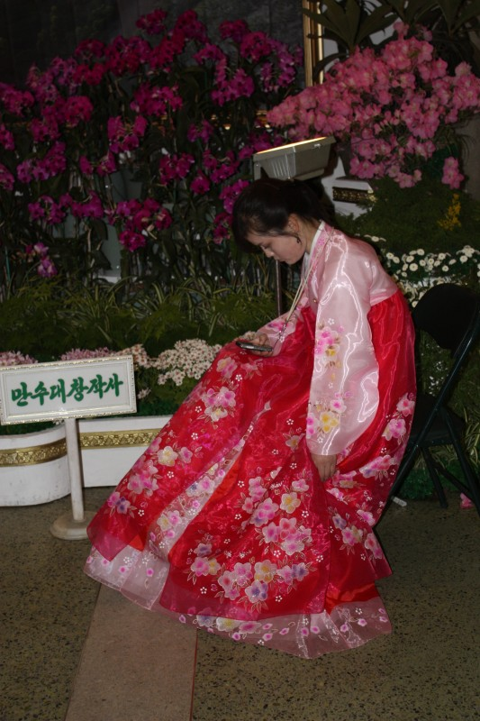 A girl checking her mobile phone at a flowershow